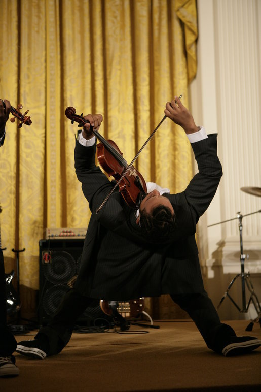 Violinist Tourie Escobar arches back almost to the floor as he performs with his brother Damein for President George W. Bush and guests Friday, June 22, 2007 in the East Room of the White House, in celebration of Black Music Month. White House photo by Eric Draper