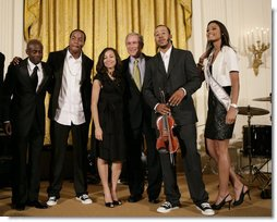 President George W. Bush thanks entertainers, from left to right, KEM, Tourie Escobar, Karina Pasian, Damien Escobar and Miss USA Rachel Smith on stage Friday, June 22, 2007 in the East Room of the White House, for their participation in a celebration of Black Music Month at the White House. White House photo by Eric Draper