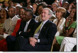 President George W. Bush, entrepreneur Bob Johnson, left, and invited guests respond to entertainers Friday, June 22, 2007 in the East Room of the White House, in celebration of Black Music Month.  White House photo by Chris Greenberg