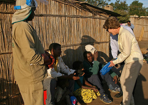 Mrs. Laura Bush hands out insecticide-treated malaria nets during a visit to a malaria spraying site Wednesday, June 27, 2007, in Mozal, Mozambique. In 2005, President Bush created the President's Malaria Initiative, an interagency effort, with a budget of $30 million. Since then the President has commited an additional $1.2 billion to the program. White House photo by Shealah Craighead