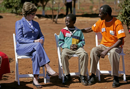 Mrs. Laura Bush talks with Raphael Lungo, 10, during a discussion with caregivers and beneficiaries of the Mututa Memorial Center Thursday, June 28, 2007 in Lusaka, Zambia. The center provides many humanitarian services including home-based care for people living with HIV/AIDS, care for orphans and promotes abstinence and faith for youth. White House photo by Shealah Craighead