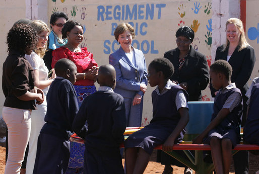 Mrs. Laura Bush and Ms. Jenna Bush stand with Zambian First Lady Mrs. Maureen Mwanawasa, dressed in red, and her daughter Ms. Chipo Mwanawasa, far left, as they watch children demonstrate how the PlayPump works at the Regiment Basic School Thursday, June 28, 2007, in Lusaka, Zambia. Working similar to a merry-go-round, the PlayPump pumps clean drinking water into a reservoir tank as the children sit on and spin it. Before the pump was installed many of the 1,200 students at the school had to bring water to school or walk long distances to find water. The school also has used the water to expand its garden, providing fresh vegetables to the more vulnerable students. White House photo by Lynden Steele