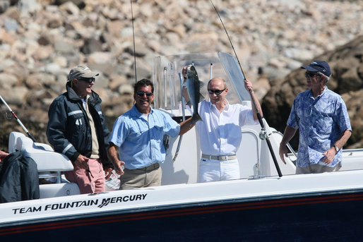 With former President George H.W. Bush and President George W. Bush looking on, Russia's President Vladimir Putin holds up his catch Monday, July 2, 2007, with the help of fishing guide Billy Bush, during a morning outing at Walker's Point in Kennebunkport, Me. White House photo by Eric Draper