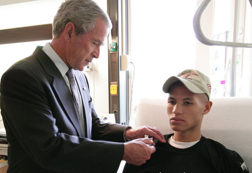 President George W. Bush pins a Purple Heart on Cpl. Joel Dulashanti of Cincinnati, during a visit Tuesday, July 3, 2007, to Walter Reed Army Medical Center in Washington, D.C., where the soldier is recovering from wounds received in Operation Iraqi Freedom. White House photo by Eric Draper