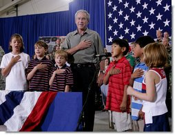 President George W. Bush joins a group of children during the Pledge of Allegiance Wednesday, July 4, 2007, at a Fourth of July visit with members of the West Virginia Air National Guard 167th Airlift Wing and their family members in Martinsburg, W. Va. White House photo by Chris Greenberg