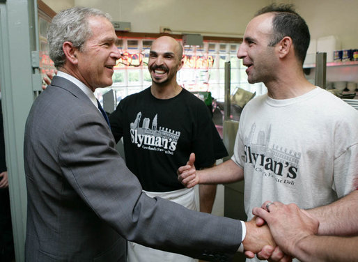 President George W. Bush is greeted by Samir Elnahass, center, and his cousin Freddie Slyman, on his arrival to Slyman's Restaurant in Cleveland, Ohio, Tuesday, July 10, 2007, where President Bush attended a luncheon with community leaders. White House photo by Chris Greenberg