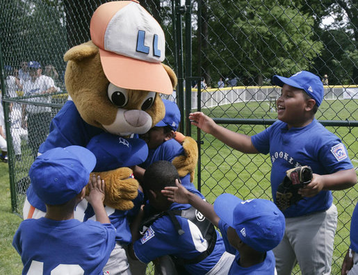 Players from the Inner City Little League of Brooklyn, N.Y. give a group hug to Dugout, the Little League mascot Sunday, July 15, 2007 at the White House Tee Ball Game, played in honor of baseball legend Jackie Robinson between Inner City and the Wrigley Little League Dodgers of Los Angeles. More about Tee Ball on the South Lawn. White House photo by Joyce N. Boghosian