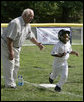 Hall of Fame baseball manager Tommy Lasorda urges on a player from the Wrigley Little League Dodgers of Los Angeles, as he runs for home against the Inner City Little League of Brooklyn, N.Y., Sunday, July 15, 2007, during the White House Tee Ball Game celebrating the legacy of Jackie Robinson on the South Lawn of the White House. Brooklyn and Los Angeles represent the two home cities of Robinson's team. More about Tee Ball on the South Lawn. White House photo by Joyce N. Boghosian