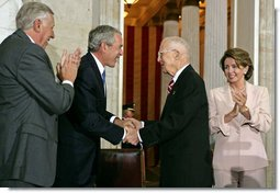 President George W. Bush congratulates Dr. Norman Bourlag during the Congressional Gold Medal Ceremony honoring the doctor's efforts to combat hunger Tuesday, July 17 , 2007, at the U.S. Capitol. Also pictured is House Majority Leader Steny Hoyer, right, and Speaker of the House Nancy Pelosi. White House photo by Chris Greenberg