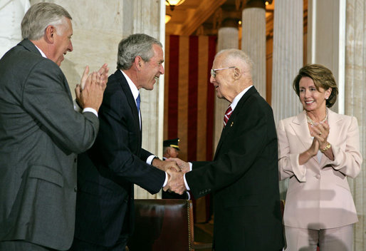 President George W. Bush congratulates Dr. Norman Bourlag during the Congressional Gold Medal Ceremony honoring the doctor's efforts to combat hunger Tuesday, July 17 , 2007, at the U.S. Capitol. Also pictured is House Majority Leader Steny Hoyer, left, and Speaker of the House Nancy Pelosi. White House photo by Chris Greenberg