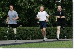 President George W. Bush jogs along the White House jogging track with wounded veterans U.S. Army Sgt.Neil Duncan (Ret.), left, and U.S. Army Specialist Max Ramsey Wednesday, July 25, 2007. White House photo by Chris Greenberg