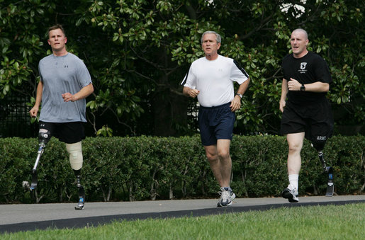 President George W. Bush jogs along the White House jogging track with wounded veterans U.S. Army Sgt. Neil Duncan (Ret.), left, and U.S. Army Specialist Max Ramsey Wednesday, July 25, 2007. White House photo by Chris Greenberg