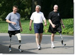 President George W. Bush meets with wounded veterans U.S. Army Sgt. Neil Duncan (Ret.), left, and U.S. Army Specialist Max Ramsey, right, for a jog Wednesday, July 25, 2007 around the South Lawn of the White House. White House photo by Eric Draper
