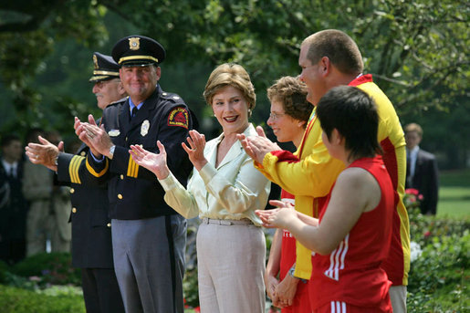 "Mrs. Laura Bush and her fellow stage participates applaud runner Karen Dickerson of Springfield, Va., during a Special Olympics Global Law Enforcement Torch Run Ceremony Thursday, July 26, 2007, in the Rose Garden. ""Karen is a tireless advocate for her fellow athletes. She's what we call a fierce competitor,"" said the President in his remarks. ""In the 2003 World Games in Ireland, Karen was told that she had a stress fracture in her leg. Yet, through sheer willpower, she won the Bronze Medal."" White House photo by Eric Draper"