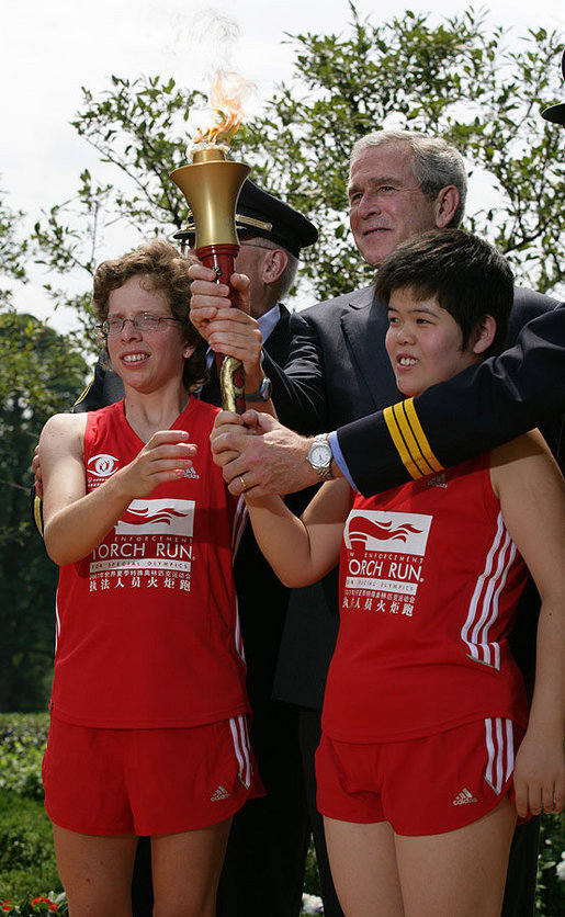 President George W. Bush and Police Chief Russ Laine of Algonquin, Ill., stand with torch runners Karen Dickerson of Springfield, Va., left, and Qiao Meili of Shanghai, China, during a Special Olympics Global Law Enforcement Torch Run Ceremony Thursday, July 26, 2007, in the Rose Garden. White House photo by Eric Draper