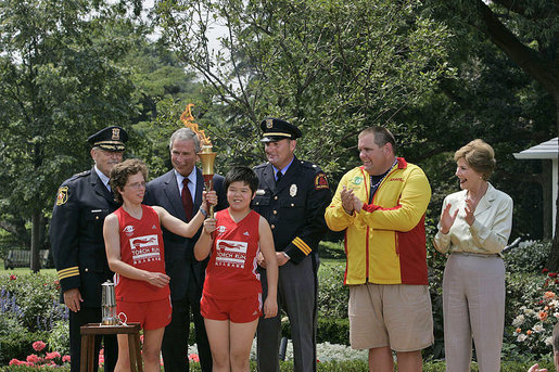 Runners Karen Dickerson of Springfield, Va., and Qiao Meili of Shanghai, China, hold up the lit torch during a Special Olympics Global Law Enforcement Torch Run Ceremony Thursday, July 26, 2007, in the Rose Garden. White House photo by Joyce N. Boghosian