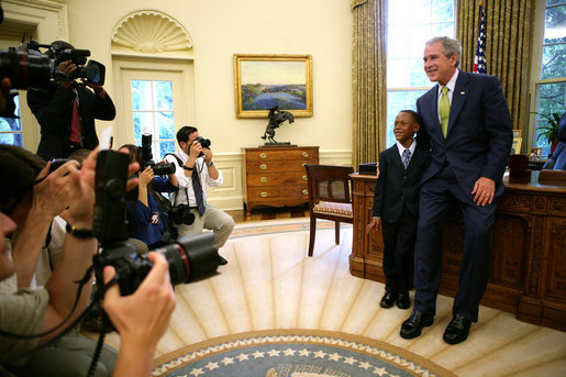 "President George W. Bush and Ezekiel ""Zeek"" Taylor, 8, of Durham, N.C., the 2007 March of Dimes National Ambassador, pose for photographers during their meeting in the Oval Office at the White House Monday, July 30, 2007. White House photo by Eric Draper"