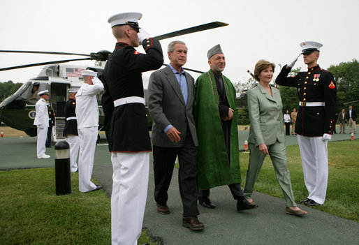 President George W. Bush and Mrs. Laura Bush walk with President Hamid Karzai of Afghanistan during an arrival ceremony at Camp David, Sunday, August 5, 2007. White House photo by Eric Draper