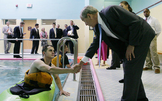 President George W. Bush meets wounded veteran Peter J. Rooney III of Cummington, Mass., a participant in the Team River Runner aquatic therapy program, during the President's visit Monday, Aug. 13, 2007 to the Washington, D.C. Veterans Affairs Medical Center indoor pool, where recuperating wounded veterans use kayaks to learn and increase their mobile skills. Team River Runner is an all-volunteer organization established in 2004 by kayakers in the Washington area that uses recreation rehabilitation through aquatic therapy activities. White House photo by Chris Greenberg