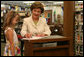Five-year-old Reese, granddaughter of the head librarian, watches as Mrs. Laura Bush signs the children's book,
