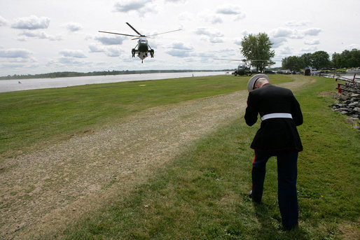 A U.S. Marine holds on to his cap and braces himself against the rotor wash of Marine One as President George W. Bush arrives Monday, Aug. 20, 2007 at the landing zone in Montebello, Canada, to attend the North American leaders' summit. White House photo by Eric Draper