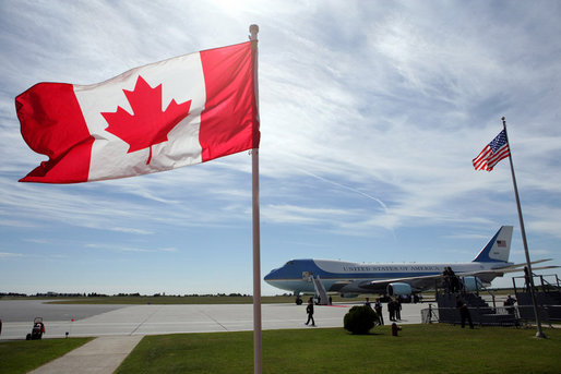 Air Force One, framed between the flags of the United States and Canada, is seen Tuesday, Aug. 21, 2007 on the tarmac in Ottawa, Canada, awaiting the arrival of President George W. Bush after the conclusion of the North American Leader's Summit in Montebello, Quebec. President Bush flew on to Minneapolis for an update meeting on the I-35W bridge collapse and Minnesota flooding. White House photo by Eric Draper