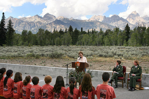 "Mrs. Laura Bush speaks to Junior Ranger participants during her visit to Grand Teton National Park Aug. 27, 2007, in Moose, Wyo. ""Children here can go back to the prehistoric era at Fossil Butte National Monument, where the remains of fish and insects, snails, turtles, birds, bats and plants are preserved in 50-million-year-old layers of rock,"" said Mrs. Bush in her address. ""Young people can discover the stories of their ancestors, the American pioneers, who migrated west along the Oregon Trail at the Fort Laramie National Area."" White House photo by Shealah Craighead"