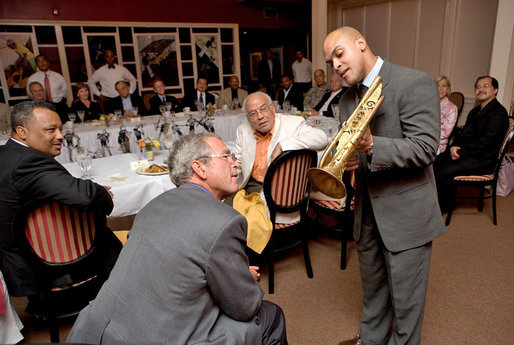 Trumpeter Irvin Mayfield shows President George W. Bush the Elysian Trumpet during a dinner with cultural and community leaders Tuesday, Aug. 28, 2007, at Dooky Chase Restaurant in New Orleans, La. Dedicated to those who perished in Hurricane Katrina, the trumpet is named for the neighborhood where Mr. Mayfield's father drowned during the storm. Representing New Orlean's spirit, the instrument is decorated with symbols of the city. White House photo by Chris Greenberg