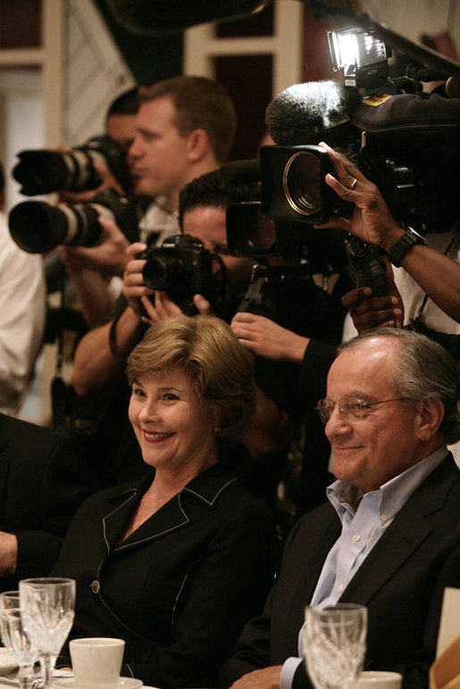 Mrs. Laura Bush and fellow dinner guest Joe Canizaro, president and CEO of Columbus Properties of New Orleans, are backed by news cameras during a dinner with Louisiana cultural and community leaders Tuesday evening, Aug. 28, 2007, at Dooky Chase's restaurant in New Orleans. President George W. Bush and Mrs. Laura Bush are visiting New Orleans and the Gulf Coast region on the second anniversary of Hurricane Katrina. White House photo by Shealah Craighead