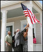 President George W. Bush helps hang a flag outside the new home of Gen White, Wednesday, Aug. 29, 2007, at a new housing development in New Orleans, during President Bush's visit to New Orleans and the Gulf Coast region on the second anniversary of Hurricane Katrina. U.S. Secretary of Housing and Urban Development Alphonso Jackson is seen at left. White House photo by Shealah Craighead
