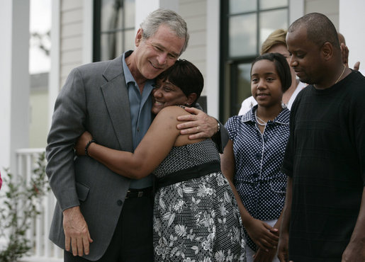 President George W. Bush is embraced by homeowner Gen White as members of her family look on, Wednesday, Aug. 29, 2007, following the President's visit to her new home in New Orleans. White House photo by Shealah Craighead