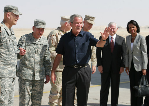 President George W. Bush waves after arriving at Al Asad Airbase, Al Anbar Province, Iraq, Monday, September 3, 2007. The greeting party from left are Lieutenant General Raymond Odierno, Commanding General, Multi-National Corps, General David Petraeus, Commander, Multi-National Force Iraq, Admiral William Fallon, Commander US Central Command, General Peter Pace, Chairman of the Joint Chiefs of Staff, Secretary of Defense Robert Gates and Secretary State Condoleezza Rice. White House photo by Eric Draper