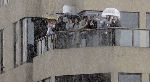 Spectators shelter themselves from a bitter rain Thursday, Sept. 6, 2007, as they wave to a motorcade carrying President George W. Bush through the streets of Sydney. White House photo by Eric Draper