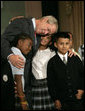 "President George W. Bush hugs students from New York Public School 76 as he makes a statement to the press about No Child Left Behind Wednesday, Sept. 26, 2007, in New York. ""Last week the school system here in New York City received the Broad Prize for Urban Education. This is one of the most prestigious education prizes in the country,"" said the President. ""The award is given every year to large urban school districts that have shown the greatest overall performance and improvement in student achievement, while narrowing the achievement gap amongst poor and minority students."" White House photo by Eric Draper"