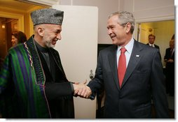 President George W. Bush welcomes Afghanistan President Hamid Karzai to a meeting at the Waldorf Astoria Hotel Wednesday morning, Sept. 26, 2007 in New York. The two leaders met following their participation in meetings at the United Nations. White House photo by Eric Draper