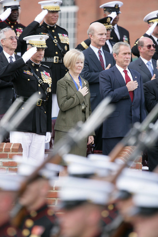 President George W. Bush stands with outgoing Joint Chiefs of Staff Chairman U.S. Marine General Peter Pace and Pace's wife, Lynne Pace, center, as troops pass in review during the Armed Forces farewell tribute in honor of General Pace and the Armed Forces hail in honor of the new Joint Chiefs of Staff Chairman Navy Admiral Michael Mullen, Monday, October 1, 2007 at Fort Myer, Virginia. White House photo by Chris Greenberg