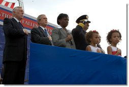 President Bush is accompanied in the Pledge of Allegiance by U.S. Senator Steny Hoyer, (D-Md.), (left), and the wife and children of firefighter Russell Schwantes of Fayetteville, Ga., during a ceremony at the National Fallen Firefighters Memorial service in Emmitsburg, Md., Sunday, Oct. 7, 2007. White House photo by Chris Greenberg