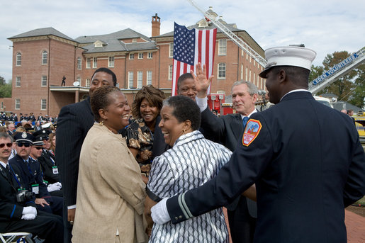 President George Bush shares a light moment with friends and family of a fallen firefighter during a ceremony at the National Fallen Firefighters Memorial in Emmitsburg, Md., Sunday, Oct. 7, 2007. White House photo by Chris Greenberg