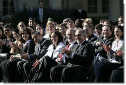 President George W. Bush joins the Rose Garden audience during a celebration Wednesday, Oct. 10, 2007, of Hispanic Heritage Month at the White House. Sitting with the President is Yamile Llanes Labrada, the wife of a political prisoner in Cuba, and Emilio Estefan. White House photo by Eric Draper