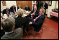 President George W. Bush participates in a lunch meeting with local business and civic leaders at the Whole Hog Cafe in Rogers, Ark., Monday, Oct. 15, 2007, speaking with Susan Barrett, left, president of Mercy Health System of Northwest Arkansas, Inc., and John A. White, Jr., chancellor of the University of Arkansas, right. White House photo by Eric Draper