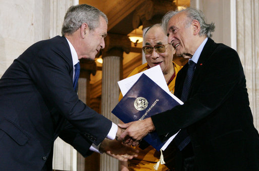 President George W. Bush, joined by The Dalai Lama, welcomes Nobel Peace Laureate Elie Wiesel, Wednesday, Oct. 17, 2007, to the ceremony at the U.S. Capitol in Washington, D.C., for the presentation of the Congressional Gold Medal to The Dalai Lama. White House photo by Chris Greenberg