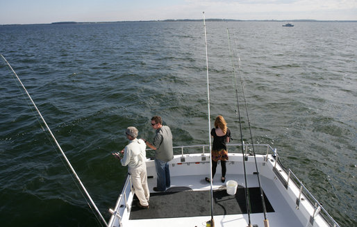 President George W. Bush, left, is seen fishing aboard a fishing boat Saturday, Oct. 20, 2007 off the coast of St. Michaels, Md., in the Chesapeake Bay, for a television interview with Chris and Melissa Fischer, hosts of ESPN's Offshore Adventures, where President Bush talked about his love of the outdoors and his signing of an Executive Order earlier in the day to protect striped bass and red drum fish species. White House photo by Eric Draper
