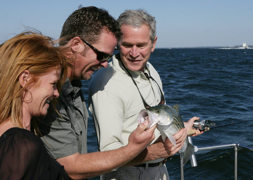 President George W. Bush is shown a fish caught by Melissa Fischer, left, by her husband, Chris Fischer, aboard a fishing boat Saturday, Oct. 20, 2007 off the coast of St. Michaels, Md., in the Chesapeake Bay, during a television interview with the Fischers, hosts of ESPN's Offshore Adventures. President Bush talked about his love of the outdoors and the Executive Order signed earlier in the day to protect striped bass and red drum fish species. White House photo by Eric Draper