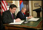 President George W. Bush and President Nambaryn Enkhbayar of Mongolia sign the Millennium Challenge Corporation Compact Monday, Oct. 22, 2007, in the Roosevelt Room of the White House. White House photo by Chris Greenberg