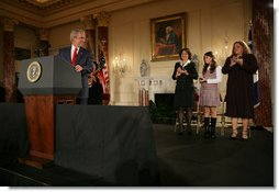 President George W. Bush acknowledges his guests, from left to right, Yamile Llanes Labrada, Melissa Gonzalez, and Marlenis Gonzalez during his remarks on Cuba policy, Wednesday, October 24, 2007, at the State Department in Washington, D.C. Labrada is the wife of Jorge Luis Garcia Paneque, a surgeon and journalist who was sentenced to 24 years in prison for speaking out against the regime. Melissa's father, Jorge Luis Gonzalez Tanquero is currently being held in a Cuban prison after being arrested for crimes against the state. White House photo by Eric Draper