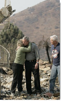 President George W. Bush hugs Kendra Jeffcoat as her husband Jay stands by in the midst of the charred rubble of their Rancho Bernardo, California home. The President met the couple during his visit Thursday, Oct. 25, 2007, to the Southern California areas ravaged by recent wildfires. White House photo by Eric Draper