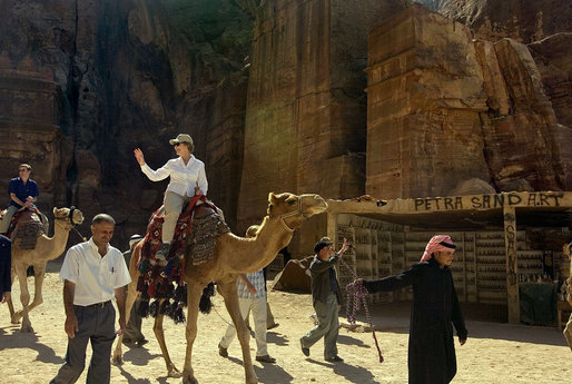 Mrs. Laura Bush takes a ride on a camel while touring Petra, an ancient city in southern Jordan Friday, Oct. 26, 2007. In 1997, a carved relief depicting two pairs of camels and camel drivers were discovered at the entrance of the city. During its time, Petra was a caravan city and trading center for the entire region. White House photo by Shealah Craighead