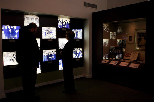 Mrs. Laura Bush, joined by Russell Caldwell, manager of visitor services at the Margaret Mitchell House and Museum in Atlanta, Ga., looks at a photo display showing images from the 1939 movie premiere of Gone with the Wind, during a tour of the famous author's home, Thursday, Nov. 1, 2007. White House photo by Shealah Craighead