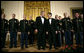 President George W. Bush and President Nicolas Sarkozy of France stand on stage with the Army Chorus in the East Room of the White House Tuesday, Nov. 6, 2007, following the after-dinner performance by the 22-member group. White House photo by Eric Draper