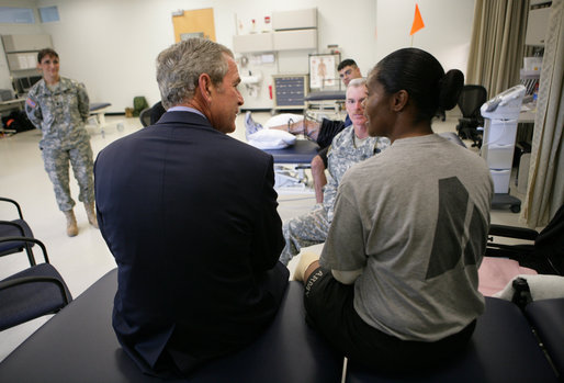 President George W. Bush speaks with a wounded soldier during his visit Thursday, Nov. 8, 2007 to the physical therapy and training area at the Center for The Intrepid at the Brooke Army Medical Center in San Antonio, Texas. White House photo by Eric Draper